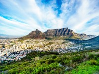 Sun setting over Cape Town Table Mountain Devils Peak Lions Head and the Twelve Apostles. Viewed from the road to Signal Hill at Cape Town South Africa shutterstock 704365027