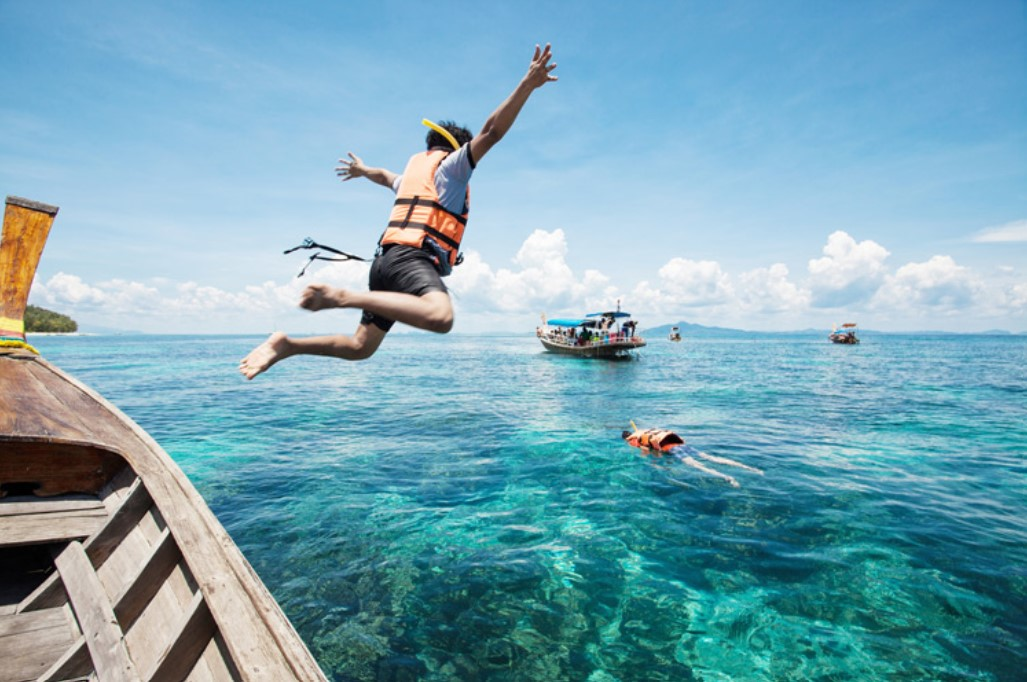 Thailand - guy jumping off a boat to snorkel